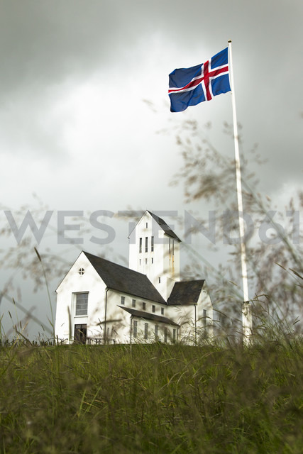 Iceland, view to church of Skalholt with blowing national flag on flaspole in the foreground - FCF000358