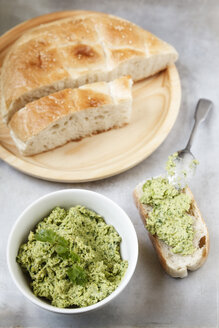 Bowl of pea coriander hummus, slices of flat bread and spoon on metal, elevated view - EVGF000724