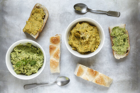 Bowls of pea coriander and carrot fennel hummus, slices of flat bread and spoons on metal, elevated view - EVGF000727