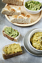 Bowls of pea coriander and carrot fennel hummus, slices of flat bread on metal - EVGF000730