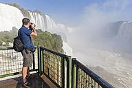 Brazil, Parana, Iguazu National Park, man photographing waterfalls from view terrace - FOF006688