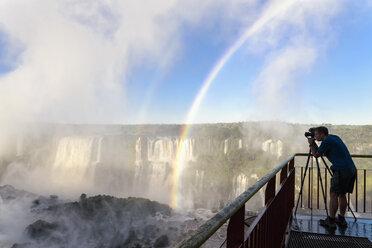 Brazil, Parana, Iguazu National Park, man photographing waterfalls - FOF006691