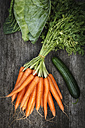 Bunch of carrots, sweetheart cabbage and cucumber on wood, elevated view - EVGF000751