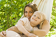 Mother and daughter relaxing in hammock - TCF004162