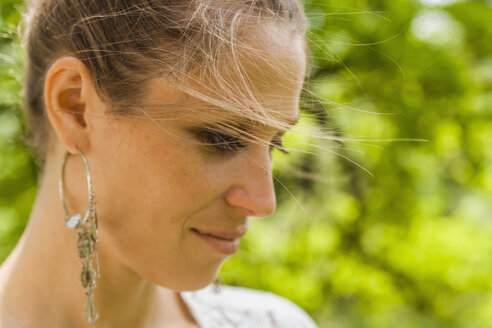Smiling woman with earring outdoors - TCF004174