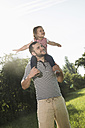 Father carrying little daughter on shoulders - UUF001516
