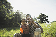 Father and his little daughter blowing soap bubbles - UUF001551
