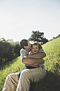 Father hugging his laughing little daughter on a meadow - UUF001586