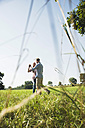 Young couple dancing together on a meadow - UUF001525