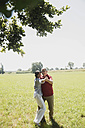 Couple of different age dancing together on a meadow - UUF001548