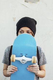Portrait of young female skate boarder holding hiding behind her skateboard - EBSF000284