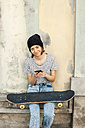 Portrait of smiling young female skate boarder with smartphone and skateboard in front of a facade - EBSF000296
