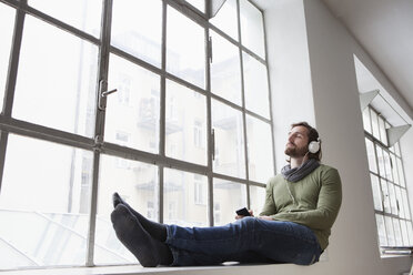 Portrait of young man sitting on window sill in an office listening music with headphones - RBF001694