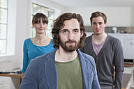 Portrait of young man with his two colleagues in the background standing in a creative office - RBF001736
