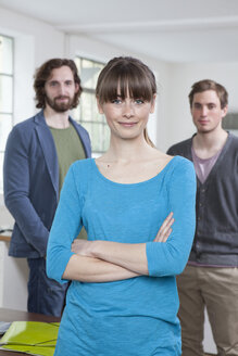 Portrait of young woman with her two colleagues in the background standing in a creative office - RBF001743