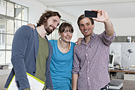 Three colleagues taking a selfie with smartphone in an office - RBF001793