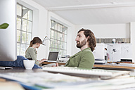 Young man relaxing at his desk in a creative office - RBF001794