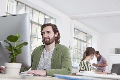 Portrait of young man working at computer in a creative office - RBF001766