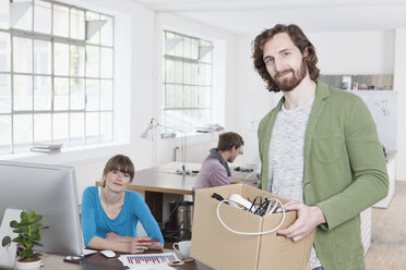 Portrait of young man with a cardboard box of power cables in a creative office - RBF001771