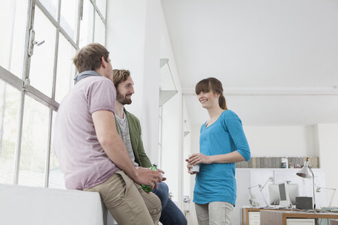 Three colleagues communicating in a creative office - RBF001738