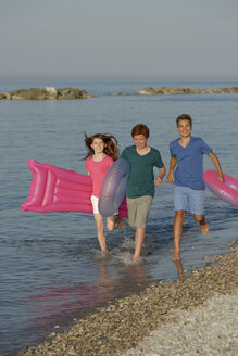 Three children running at waterside of Adria with air bed and floating tires - LBF000893