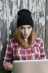 Portrait of a young woman with laptop in front of a wooden wall - SEF000809