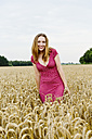 Portrait of a smiling young woman standing in a grainfield - SEF000812