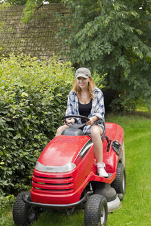Smiling young woman driving on a lawn-mower - SEF000820