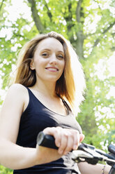 Portrait of a smiling young woman holding handlebar of a bicycle - SEF000826