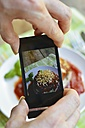 Man taking a photo of a dish, Stuffed Portobello Mushrooms, with a smart phone - HAWF000426