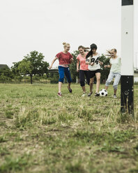 Four teenage girls playing soccer on a football ground - UUF001565