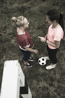Two teenage girls communicating on a football ground, elevated view - UUF001573
