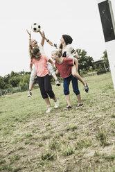Four teenage girls having fun on a soccer field - UUF001576