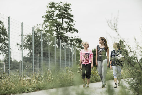 Three teenage girls with soccer ball and skateboard walking side by side - UUF001582