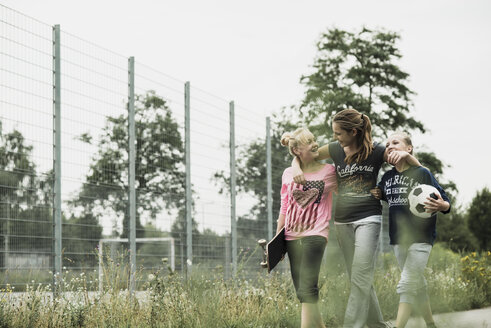 Three happy teenage girls with soccer ball and skateboard walking side by side - UUF001584