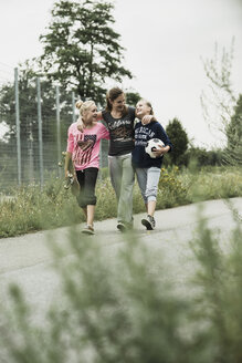Three happy teenage girls with soccer ball and skateboard walking side by side - UUF001585