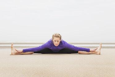 Belgium, Flanders, woman doing yoga exercises on the beach - GW003712