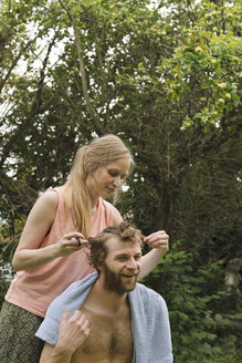 Young woman cutting hair of her boyfriend in the garden - LAF001184