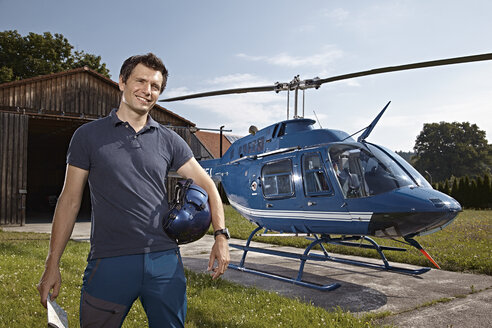 Germany, Bavaria, Landshut, Helicopter pilot holding map - KDF000036