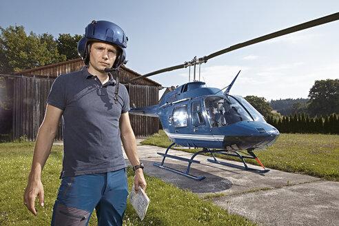 Germany, Bavaria, Landshut, Helicopter pilot holding map - KDF000037