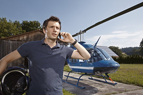 Germany, Bavaria, Landshut, Helicopter pilot using mobile phone - KDF000067