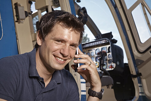 Germany, Bavaria, Landshut, Helicopter pilot using mobile phone - KDF000080