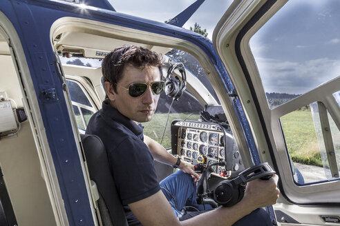Germany, Bavaria, Landshut, Helicopter pilot in cockpit - KDF000069