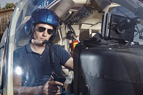 Germany, Bavaria, Landshut, Helicopter pilot in cockpit - KDF000042