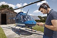 Germany, Bavaria, Landshut, Helicopter pilot checking mobile phone - KD000056