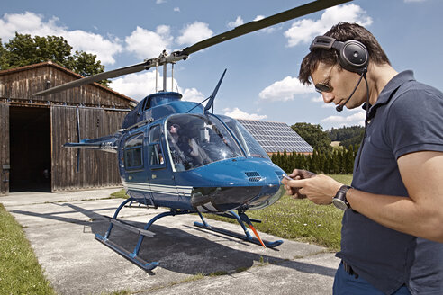 Germany, Bavaria, Landshut, Helicopter pilot checking mobile phone - KD000056