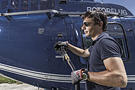 Germany, Bavaria, Landshut, Helicopter pilot refuelling aircraft - KDF000073