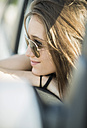 Portrait of smiling teenage girl with sunglasses sitting in a car - UUF001590