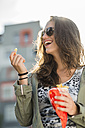Portrait of laughing teenage girl wearing sunglasses holding paperbag of French Fries - UUF001629