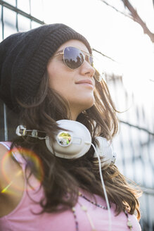 Portrait of smiling teenage girl with headphones wearing sunglasses and wool cap - UUF001598